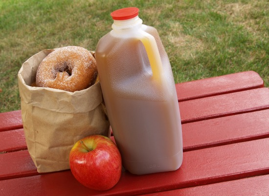 apple cider an apple and a bag of cinnamon-sugared donuts on a red picnic table